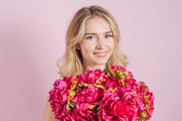 Bouquet de roses de fleurs rouges en face de la souriante jeune femme sur fond rose