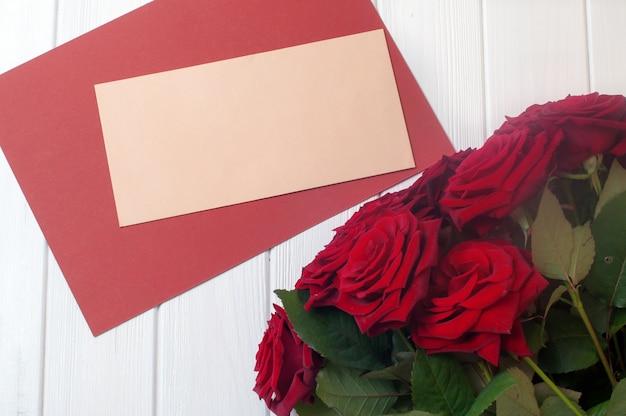 Bouquet de roses fleursprès de l'enveloppe de courrier vide