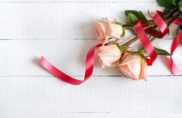 Bouquet de roses sur un fond en bois blanc. le concept de la saint-valentin.