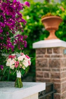 Bouquet de roses sur fond de bougainvilliers sur pilier en pierre
