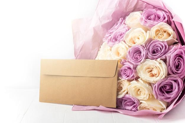 Bouquet de roses fraîches blanches et violettes étonnantes et enveloppe artisanale
