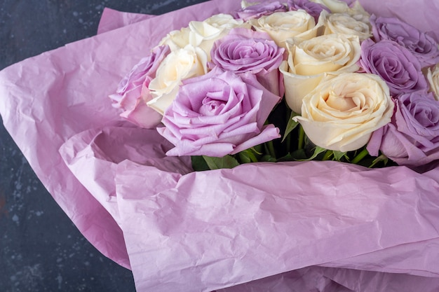 Bouquet de roses fraîches blanches et violettes étonnantes en papier kraft sur fond blanc