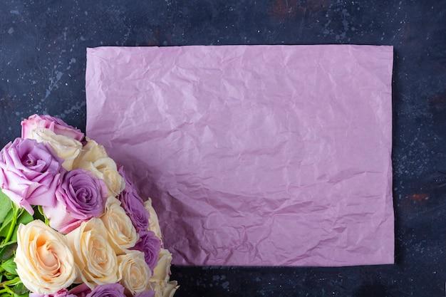 Bouquet de roses fraîches blanches et violettes incroyables et feuille de papier kraft sur fond sombre.