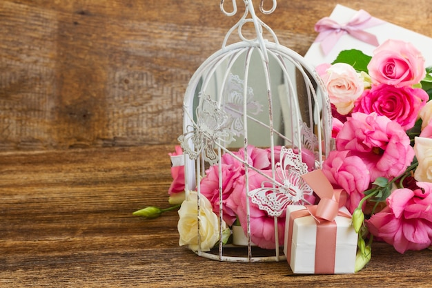 Bouquet de roses fraîches roses et blanches et de fleurs d'eustoma avec présent fort sur fond de bois