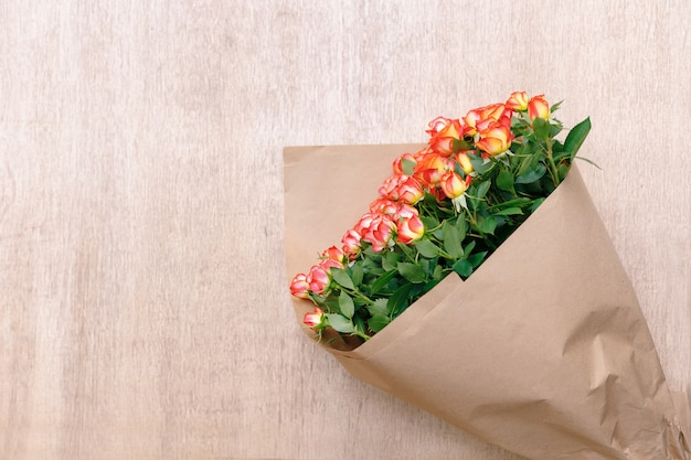 Un bouquet de roses magnifiques fraîches en papier kraft sur un fond en bois