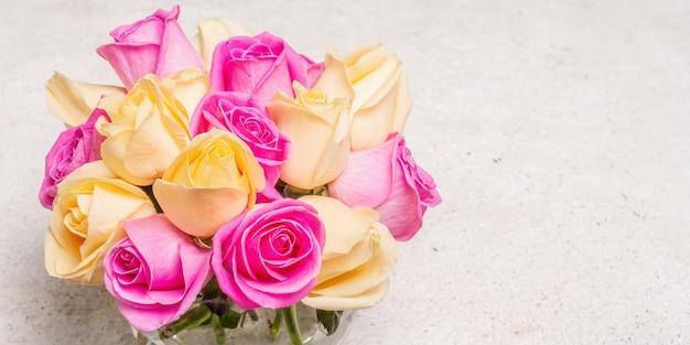 Bouquet de roses multicolores fraîches dans un vase. le concept festif pour les mariages, les anniversaires, le 8 mars, la fête des mères ou la saint-valentin. carte de voeux, fond clair, bannière