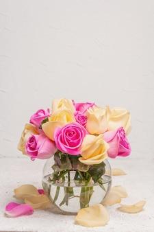 Bouquet de roses multicolores fraîches dans un vase. le concept festif pour les mariages, les anniversaires, le 8 mars, la fête des mères ou la saint-valentin. carte de voeux, fond clair
