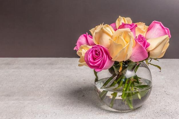 Bouquet de roses multicolores fraîches dans un vase. le concept festif pour les mariages, les anniversaires, le 8 mars, la fête des mères ou la saint-valentin. carte de voeux, fond sombre