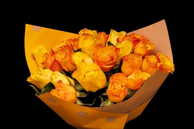 Un bouquet de roses oranges dans un emballage cadeau est isolé sur fond noir. photo de haute qualité
