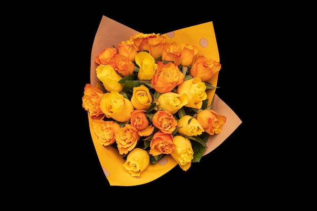 Un bouquet de roses oranges est isolé sur un fond noir. vue d'en-haut. photo de haute qualité