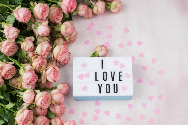 Bouquet de roses roses, coeurs roses et une assiette avec l'inscription: je t'aime