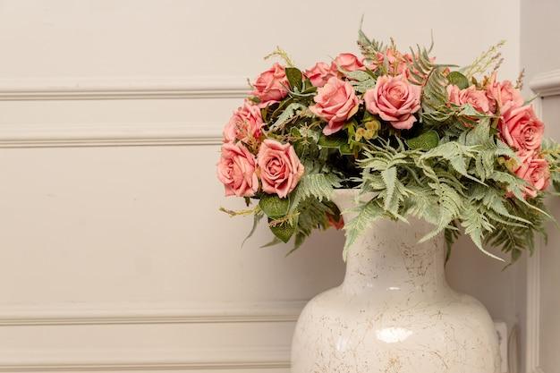 Bouquet de roses roses dans un vase en céramique de style classique. décoration d'intérieur shbby chic.