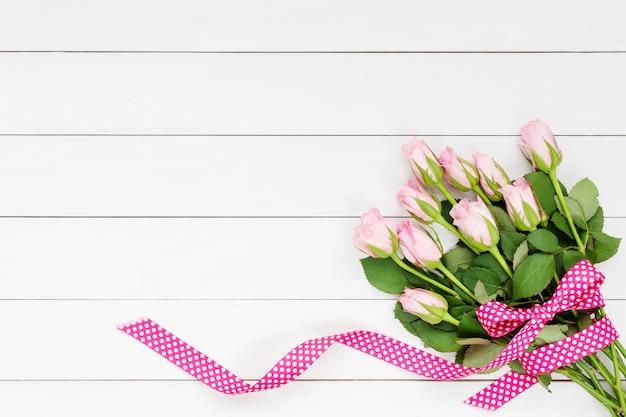 Bouquet de roses roses décorées avec un ruban sur un fond en bois blanc.