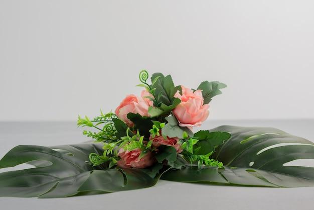 Bouquet de roses roses avec des feuilles sur une surface grise