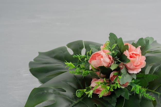 Bouquet de roses roses avec des feuilles sur une surface grise.
