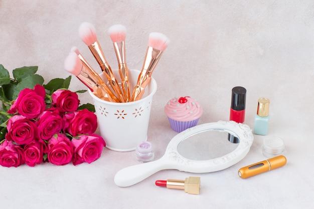 Bouquet de roses roses, miroir, pinceaux et maquillage