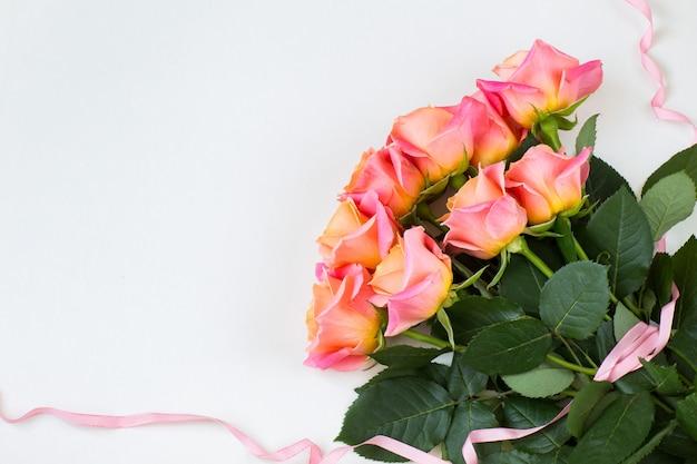 Un bouquet de roses roses noué avec un ruban rose