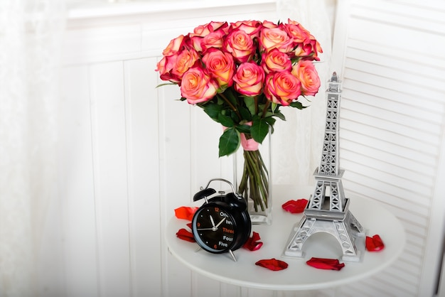 Un bouquet de roses roses sur une table avec une tour eiffel miniature