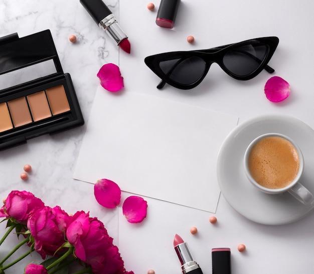 Bouquet de roses roses, tasse de café, lunettes de soleil, correcteur et rouge à lèvres sur un tableau blanc.