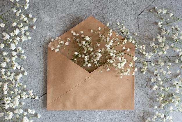 Bouquet de roses roses tendres avec une carte de voeux vierge et une enveloppe