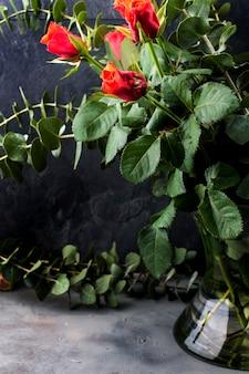 Bouquet de roses rouges et beaucoup de feuilles vertes dans un vase sur fond noir