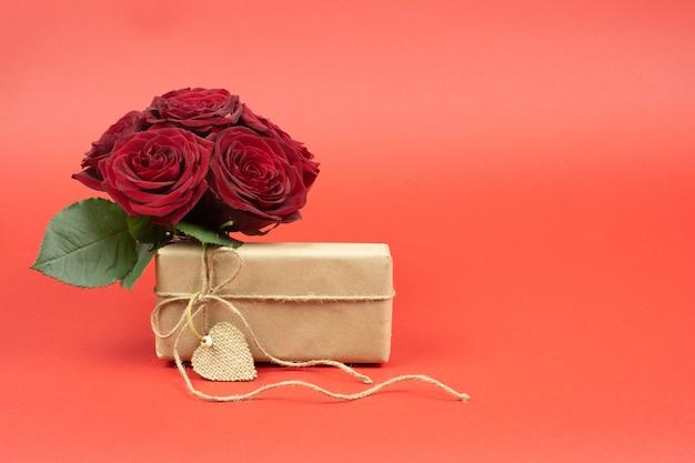 Bouquet de roses rouges avec boîte de papier craft sur rouge