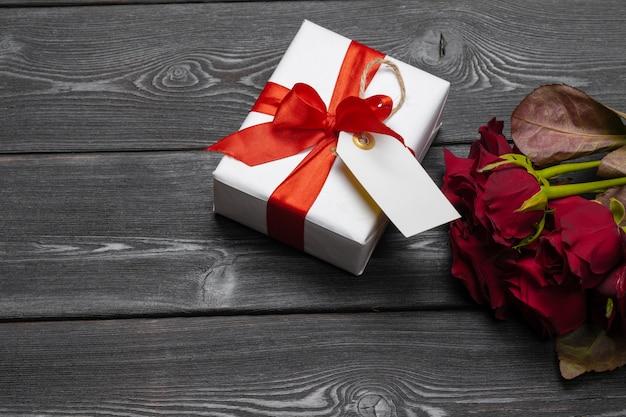 Un bouquet de roses rouges, cadeau et coeurs sur la table. journée de la femme ou saint-valentin. espace de copie