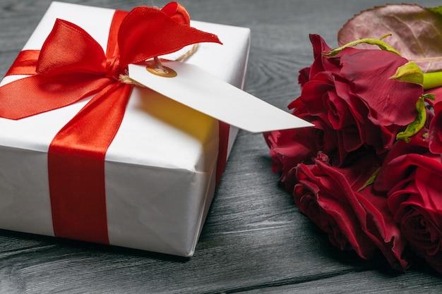 Un bouquet de roses rouges, cadeau et coeurs sur la table