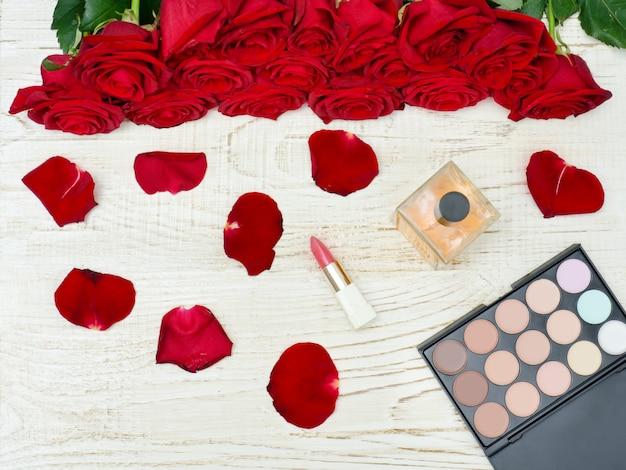 Bouquet de roses rouges, palette de parfum, rouge à lèvres et fard à paupières sur une table en bois blanche.