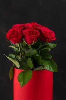 Bouquet de roses rouges en pot rouge sur fond sombre.