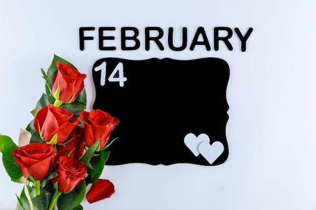 Bouquet de roses rouges avec texte le 14 février et tableau noir maquette isolé sur fond blanc. fête des mères ou saint valentin.
