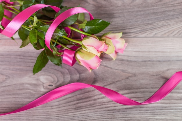 Bouquet de roses avec ruban rose sur bois