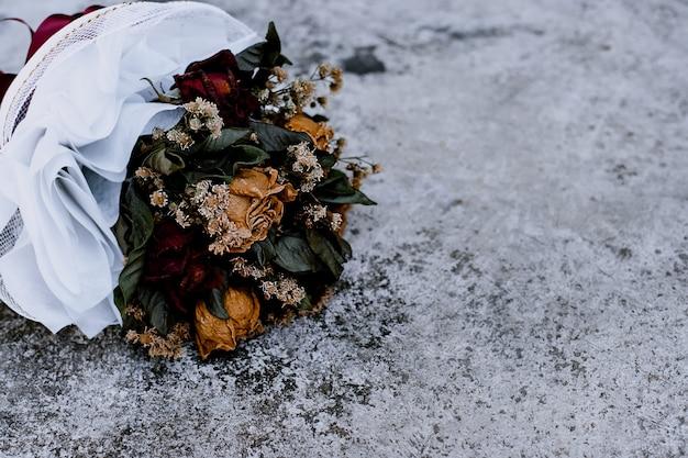 Bouquet de roses séchées sur le sol en ciment. bouquet de roses séchées rouges à attacher avec une corde.