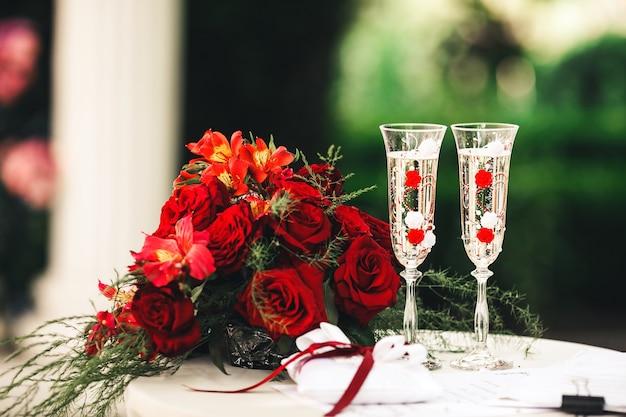 Un bouquet rouge, de belles verres à champagne et un oreiller pour les alliances se trouvent sur la table.