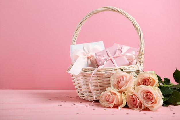 Bouquet de la saint-valentin et panier-cadeau sur fond rose