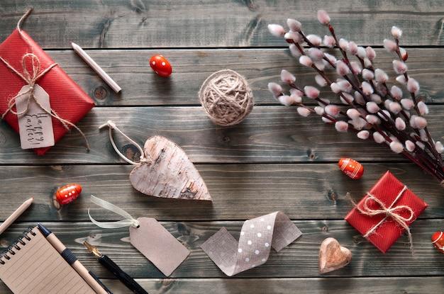 Bouquet de saules, cadeaux emballés, cahier, cœur en bois et œufs de pâques, cordon et étiquettes sur bois rustique