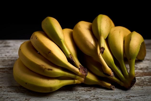 Bouquet de savoureuses bananes jaunes mûres sur une planche de bois clair