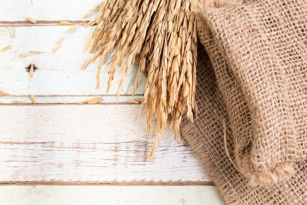 Bouquet sec épis de riz thai jusmine et jute ou un sac sur table en bois., vue de dessus