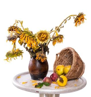 Bouquet sec de tournesols dans un vase et de pommes sur la table. automne nature morte