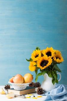 Bouquet de tournesols dans un vase blanc avec des pommes