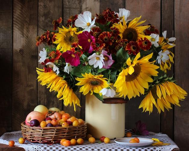 Bouquet de tournesols, pommes et prunes.