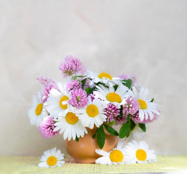 Bouquet de trèfle et camomille dans un vase sur fond clair. bouquet d'été de fleurs de jardin et des champs. nature morte aux pâquerettes. mise au point sélective