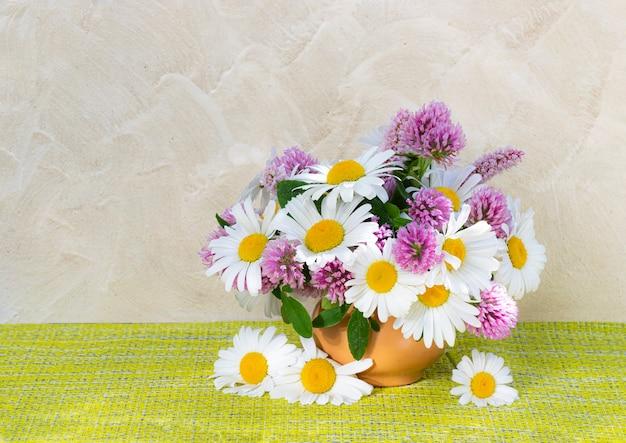 Bouquet de trèfle et camomille dans un vase sur fond clair. bouquet d'été de fleurs de jardin et des champs. nature morte aux pâquerettes.