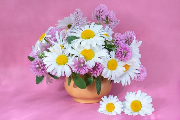 Bouquet de trèfle et camomille dans un vase sur fond clair. bouquet d'été de fleurs de jardin et des champs. nature morte sur fond rose.