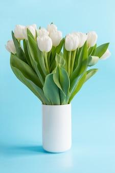Bouquet de tulipe blanche dans un vase sur bleu.