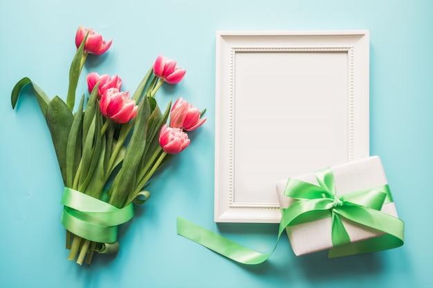 Bouquet de tulipe rouge et coffret cadeau sur fond bleu. t