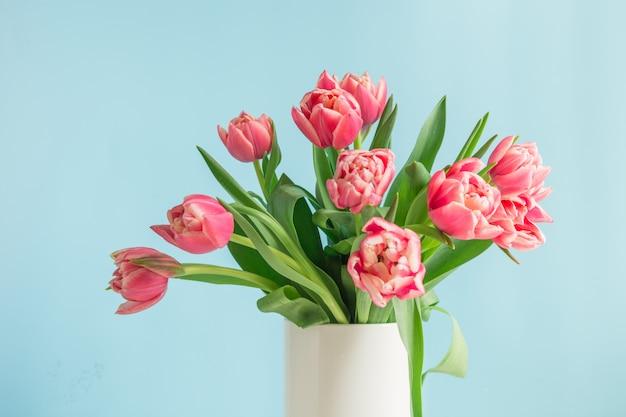 Bouquet de tulipe rouge dans un vase sur bleu. fête des mères.