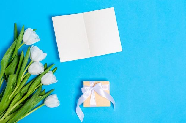 Bouquet de tulipes blanches avec une carte de voeux et un coffret cadeau sur un bleu clair