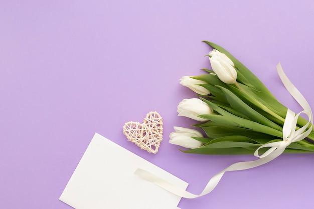 Bouquet de tulipes blanches, enveloppe et coeur sur violette