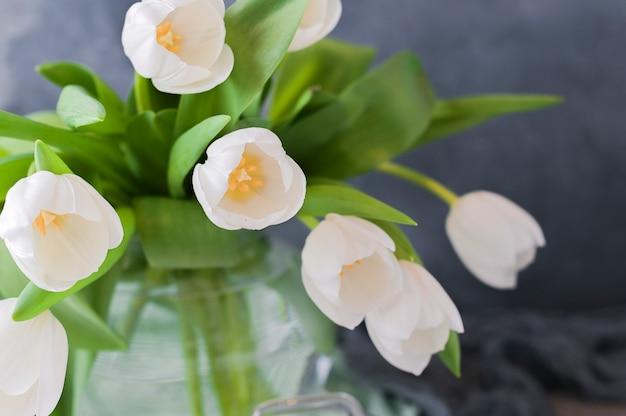 Bouquet de tulipes blanches sur fond gris.